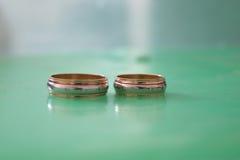 Wedding золотые кольца на зеленой предпосылке Стоковое Фото