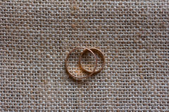 Wedding золотые кольца на предпосылке циновок Стоковое Изображение RF