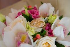 2 wedding кольца золота при диамант лежа на bride& x27; букет s белых орхидей и розовых цветков Стоковые Изображения