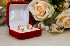 2 wedding кольца золота с диамантами в красной коробке около bride& x27; букет s красного цвета и белых роз Стоковое Изображение RF
