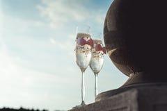 2 wedding стекла шампанского с смычком на каменных перилах Прогулка озера на заходе солнца Стоковое Фото