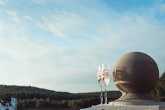 2 wedding стекла шампанского с смычком на каменных перилах Прогулка озера на заходе солнца Стоковое фото RF