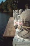 2 wedding стекла шампанского с смычком на каменных перилах Прогулка озера на заходе солнца Стоковые Фото