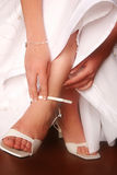 Wedding #1. Hands of bride putting on wedding shoes Royalty Free Stock Photos