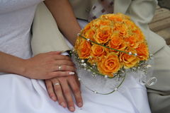 Wedding. Just  married couple sits on the banch with an orange bouquet Royalty Free Stock Photos