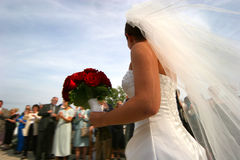 After the wedding. Bride with bouquet, leaving reception with groom, surrounded by well-wishers Royalty Free Stock Photography