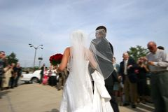 After the wedding. Bride with bouquet, leaving reception with groom, surrounded by well-wishers stock images