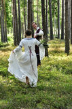 Wedding. Princess bride running in the wood an her knight wait for her / wedding royalty free stock photos