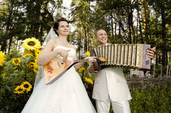 Wedding. Fiancee blow the balalaika, bridegroom play on accordion, wedding humour photo royalty free stock image