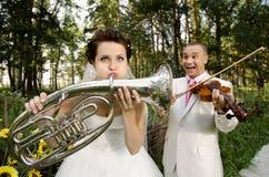 Wedding. Fiancee blow the trumpet,  bridegroom play on violin, wedding  humour photo Stock Photos