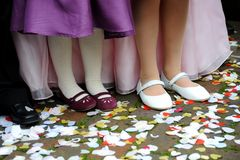 At The Wedding. Childrens shoes amongst thrown wedding confetti royalty free stock photos