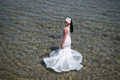 Wedding abroad. Wedding ceremony seashore. Bride white wedding dress stand in sea water. Wet wedding dress hot sunny day. Bride happy enjoy summer vacation royalty free stock photography