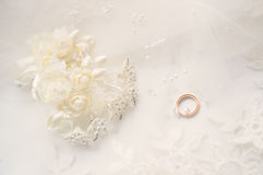 Wedding Accessories. Gold wedding rings and wedding jewelry of artificial flowers on a background of white tulle Stock Photo