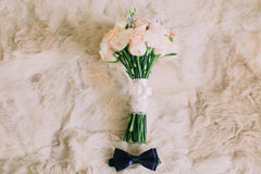 Wedding accessories: blue bow tie of groom, bridal roses bouquet  on the white fur. Stock Photo
