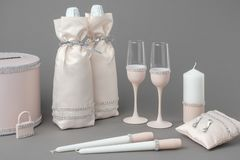 Wedding accessories: bottles of champagne in bags, wine glasses, candles, box for money, wedding lock and pillow for rings. Wedding accessories: bottles of royalty free stock image