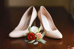 Wedding accessories bouquet red, white and pink flowers for groom and beige shoes on dark wooden background.  Royalty Free Stock Photos