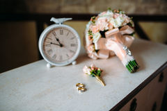 Wedding accessories. Boutonniere, Golden rings, a beautiful bouquet of flowers on white textured table. Concept of bride Stock Image
