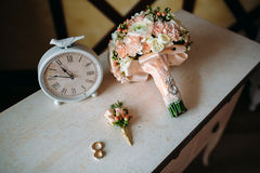 Wedding accessories. Boutonniere, Golden rings, a beautiful bouquet of flowers on white textured table. Concept of bride Stock Photos