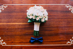 Wedding accessories: bow tie of groom and beautiful bridal bouquet on a rustic wooden background Stock Image
