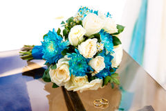 Wedding accessories. The bride's bouquet and wedding rings. Stock Photos