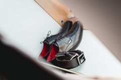 Brown bow tie lies on a belt, leather shoes. Grooms wedding morning. Wedding accessories. Brown bow tie lies on a belt, leather shoes on window sill. Grooms Stock Photos
