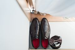 Brown bow tie lies on a belt, leather shoes. Grooms wedding morning. Wedding accessories. Brown bow tie lies on a belt, leather shoes on window sill. Grooms Royalty Free Stock Photography