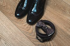 Brown bow tie lies on a belt, leather shoes. Grooms wedding morning. Wedding accessories. Brown bow tie lies on a belt, leather shoes on a wooden floor. Grooms Royalty Free Stock Photography