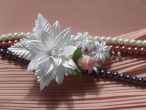 Wedding accessories:  buttonhole and a string of pearls Royalty Free Stock Photo