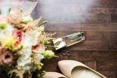 Wedding accessories. Gold perfume, golden rings, wedding shoes and a part of bridal bouquet. Wedding details Royalty Free Stock Photos