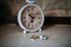 Wedding accessories. Gold rings and cufflinks on white textured table and clock on the background.  Stock Images