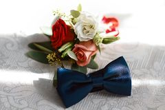 Wedding accessories of the groom, dark blue butterfly with a flower bouquet Royalty Free Stock Photo