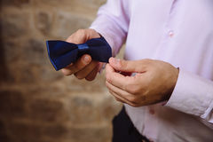 Wedding accessories. Groom holding blue bow tie in his hand Stock Image