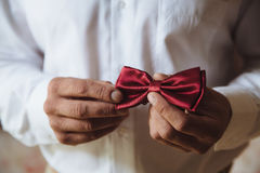 Wedding accessories. Groom holding red bow tie in his hand Stock Photo