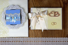 Wedding accessories and invitations to frame light wooden table Royalty Free Stock Images