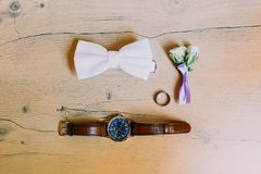 The wedding accessories. The lovely rose boutonniere, hand watch, silver ring and bow-tie on the rustic floor. Royalty Free Stock Photography