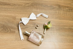 Wedding accessories. Pink perfume, bridal earrings with diamonds, white bowtie and boutonniere with small roses Stock Image