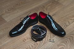 Brown bow tie lies on a belt, leather shoes. Grooms wedding morning. Wedding accessories, wedding rings. Brown bow tie lies on a belt, leather shoes on a wooden Royalty Free Stock Images