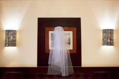 Wedding accessories. Veil hangs over the bed between two lamps. Stock Images