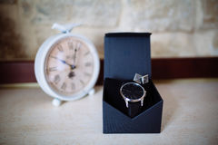 Wedding accessories. Watches and cufflinks on white textured table and clock on the background.  Stock Photography