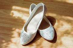 Wedding accessories, white bridal shoes with pebbles on low, wooden background, lace shadow.  Royalty Free Stock Image