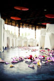 Wedding Aisle. Rose petals laid out on the concrete floor for a wedding where the bride will walk down the aisle. Red Chinese umbrellas used as decorative royalty free stock images