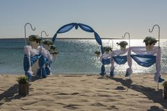 Wedding aisle setup on tropical beach. Setup of wedding day marriage aisle with drapes and arch on sandy tropical beach paradise to open ocean background royalty free stock photography