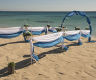 Wedding aisle setup on tropical beach. Setup of wedding day marriage aisle with drapes and arch on sandy tropical beach paradise to open ocean background stock image