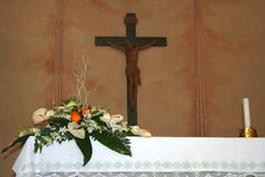 Wedding altar with flowers. Bouquet of wedding flowers sitting on a church altar, crucifix on background Stock Photo