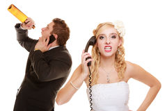 Wedding. Angry bride and groom talking on phone Royalty Free Stock Photos