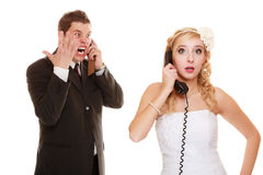 Wedding. Angry bride and groom talking on phone Royalty Free Stock Image