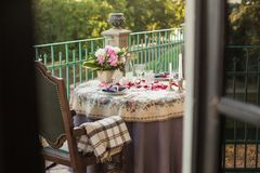 Romantic decor of the festive table in the restaurant with candles, flowers, rose petals royalty free stock images