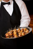 Wedding appetizers. A waiter carries a platter of appetizers during a catered social event Stock Photography