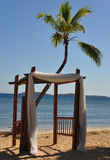 Wedding Arbor in the Caribbean. A wedding arbor on the beach in the Caribbean draped in white fabric with a palm tree and the ocean in the background Stock Images