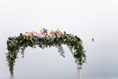 Wedding arch. Beautiful arrangement of flowers decorating a wedding ceremony arch stock image